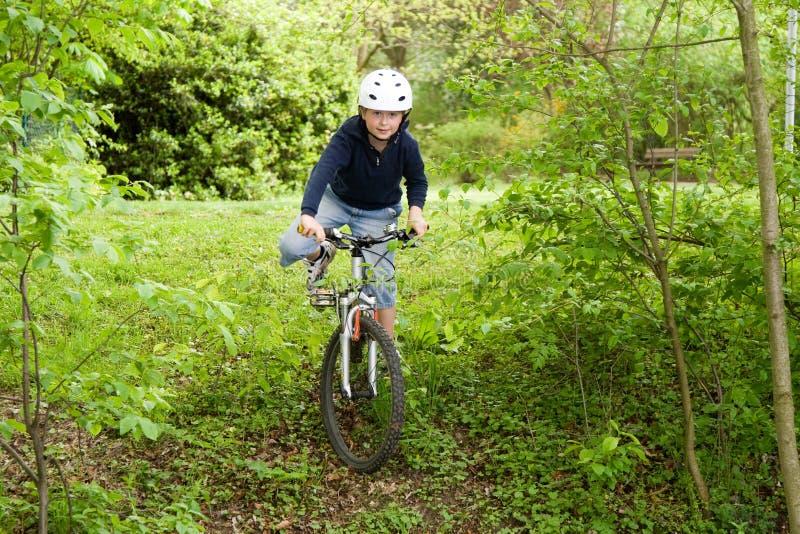 Menino novo com a bicicleta de montanha na excursão imagem de stock