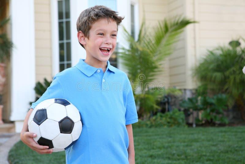 Menino novo com esfera de futebol fotografia de stock royalty free