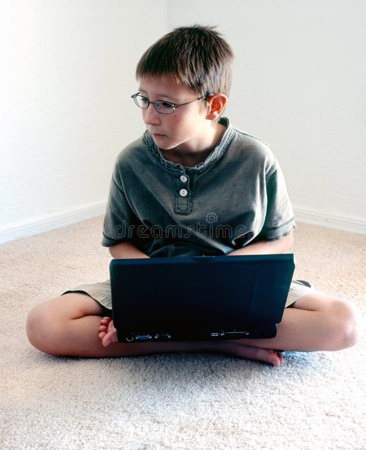 Menino novo com laptop foto de stock