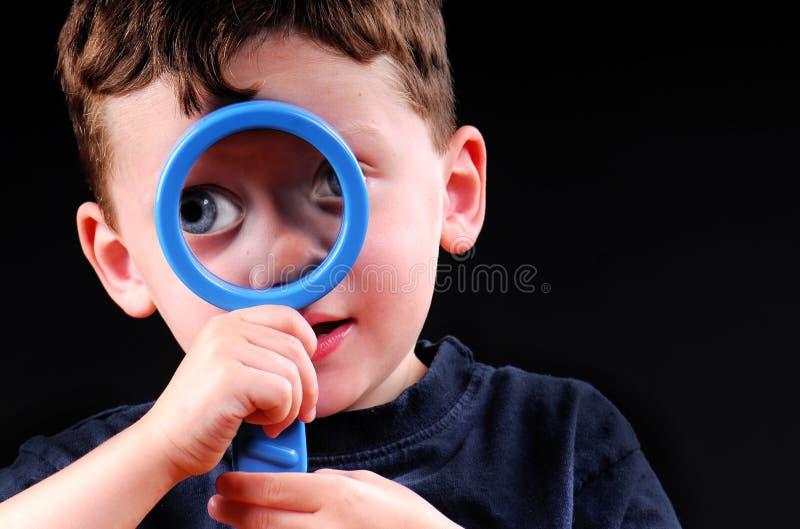 Menino novo com Magnifier fotografia de stock