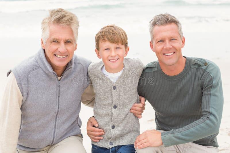 Menino novo com seus pai e avô foto de stock