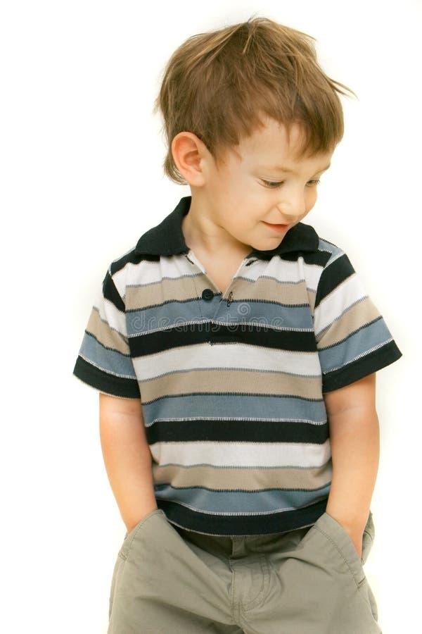 Menino novo com suas mãos em uns bolsos fotografia de stock