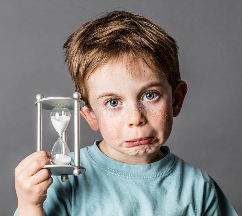 Menino novo desapontado com uma ampulheta para o conceito do tempo imagem de stock