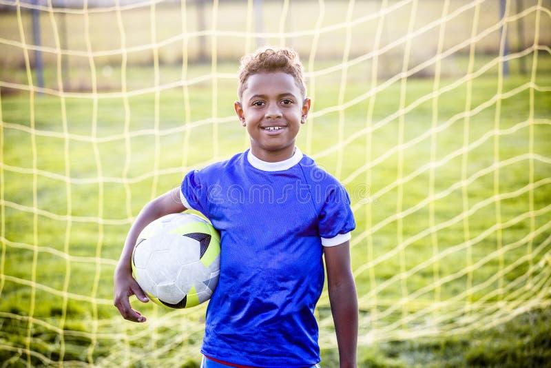 Menino novo diverso em uma equipe de futebol da juventude fotos de stock