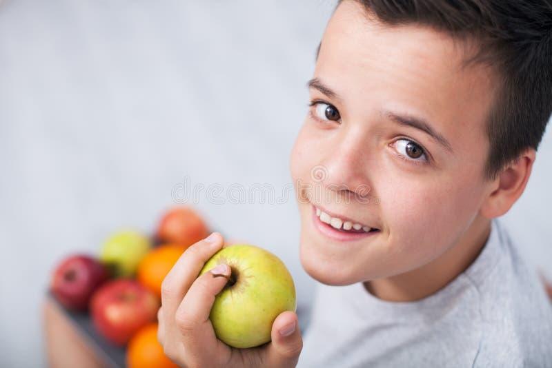 Menino novo do adolescente que guarda uma maçã - olhando acima imagens de stock