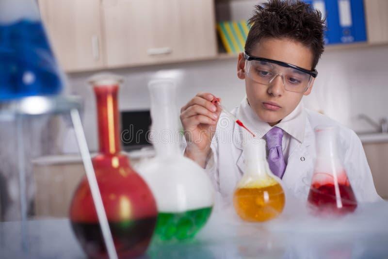 Menino novo do cientista que trabalha em um laboratório imagens de stock
