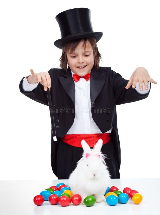 Menino novo do mágico que executa um truque de easter imagem de stock