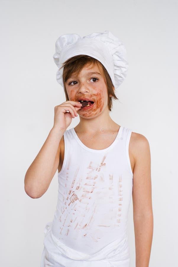 Menino novo do padeiro que come o chocolate imagem de stock royalty free