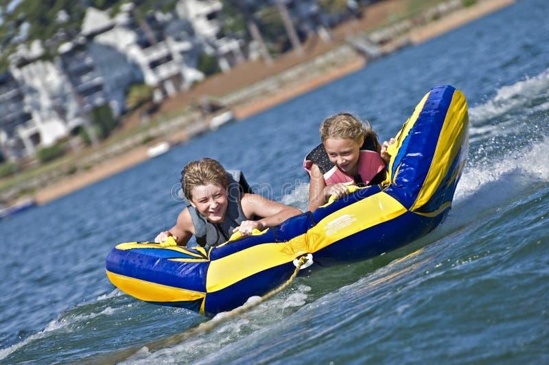 Menino novo e menina que montam uma câmara de ar na água imagens de stock royalty free