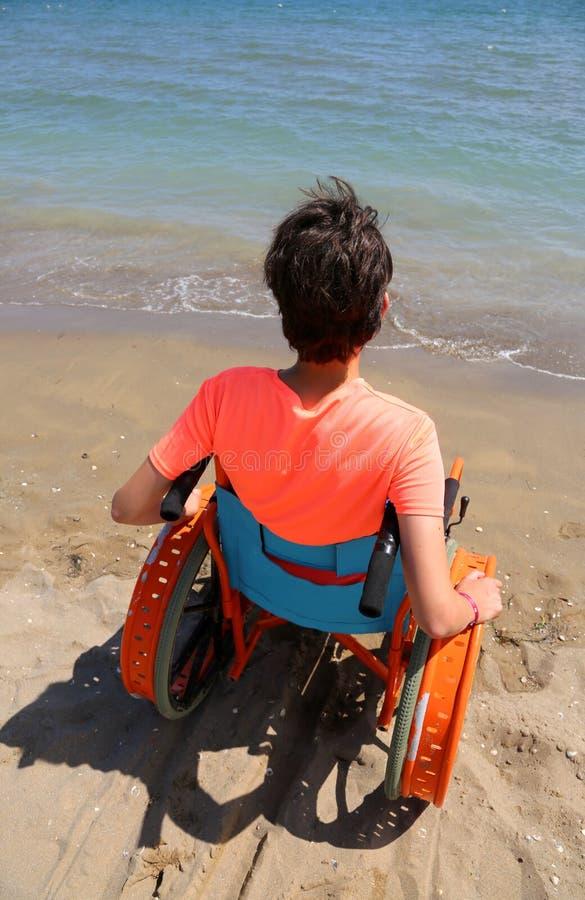 Menino novo em uma cadeira de rodas pelo mar imagens de stock