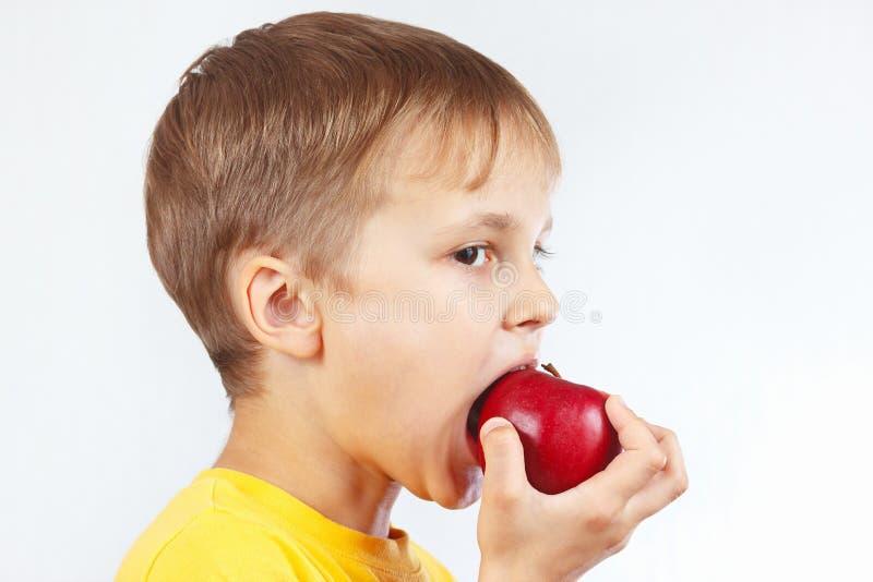 Download Menino Novo Em Uma Camisa Amarela Que Come A Maçã Vermelha Foto de Stock - Imagem de suculento, dieta: 65575024