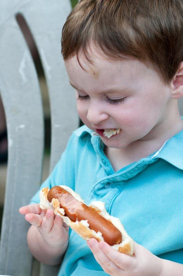 Menino novo exterior comendo um cachorro quente grande fotos de stock royalty free