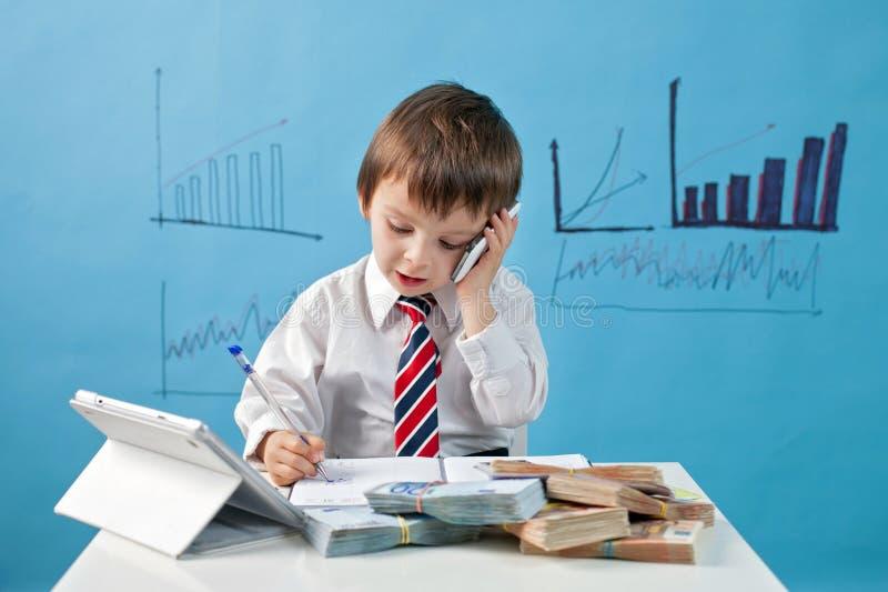 Menino novo, falando no telefone, escrevendo notas, dinheiro e tabuleta imagens de stock