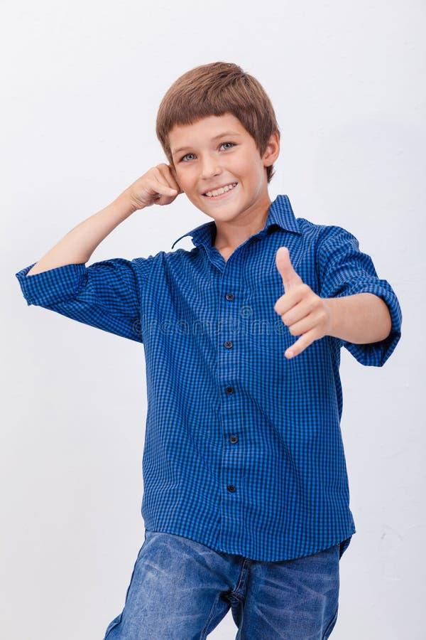 Menino novo feliz com chamada do gesto sobre o branco imagem de stock royalty free