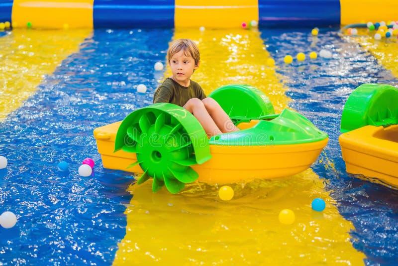 Menino novo feliz no barco que aprecia o jogo no parque de diversões imagens de stock