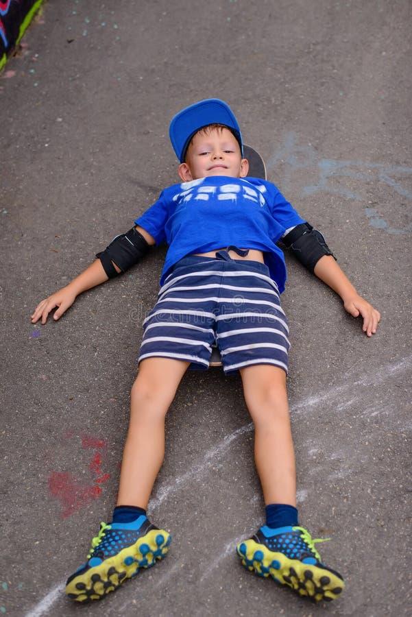 Menino novo feliz que relaxa em seu skate imagem de stock royalty free