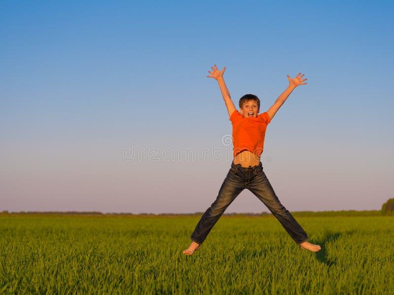 Menino novo feliz que salta fora com braços aumentados imagens de stock