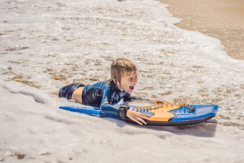 Menino novo feliz que tem o divertimento na praia em férias, com placa da dança imagem de stock royalty free