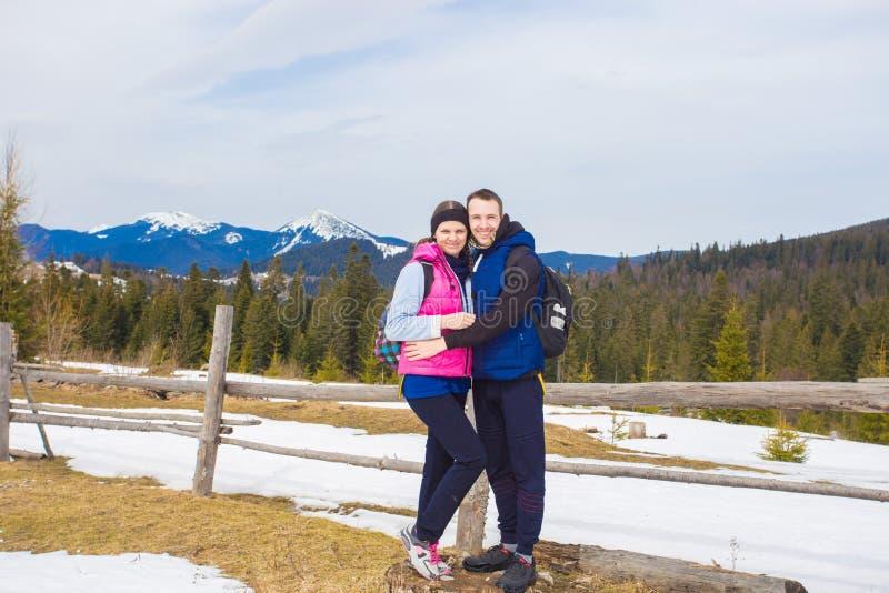 Menino novo feliz sobre a montanha com árvores cobertos de neve que admira os pares bonitos do viewLove do vale que caminham nas  imagens de stock royalty free
