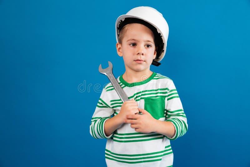 Menino novo furado no capacete protetor que levanta com chave imagens de stock royalty free