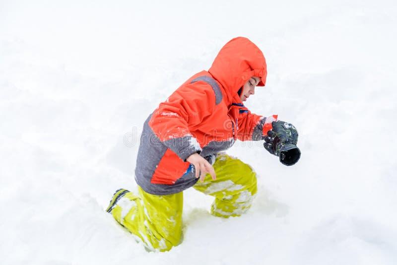 Menino novo isolado no fundo da neve Menino novo no kne do snowsuit imagens de stock royalty free