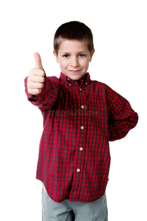 Menino novo na camisa de manta que dá os polegares acima imagem de stock royalty free
