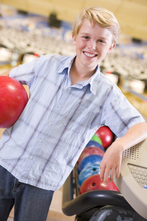 Menino novo na esfera da terra arrendada da aléia de bowling fotos de stock royalty free