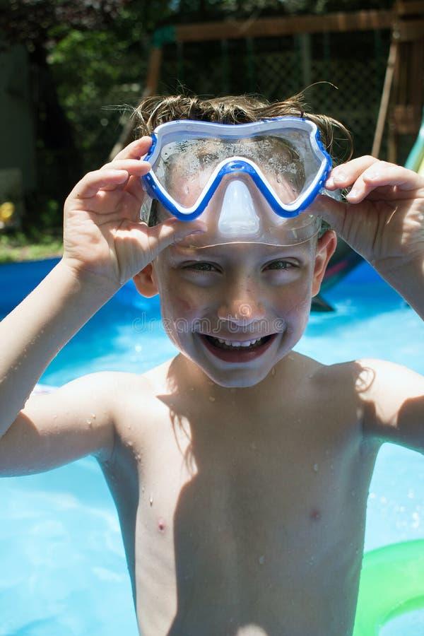 Menino novo na máscara da natação na associação do quintal fotografia de stock