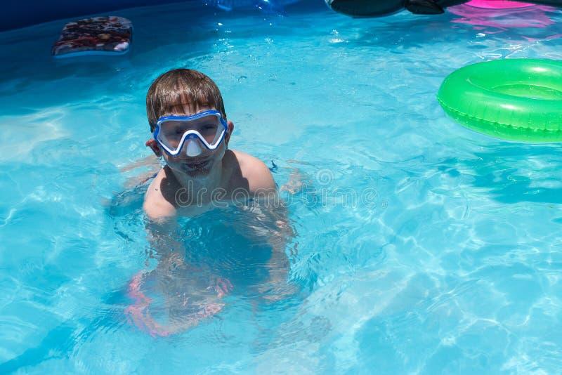 Menino novo na máscara da natação na piscina com flutuador verde fotos de stock