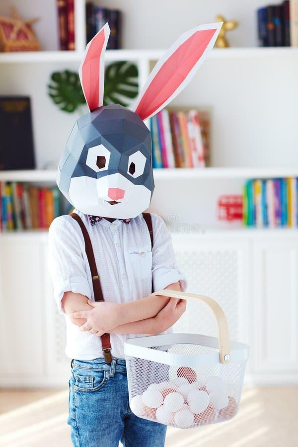 Menino novo na máscara poligonal do coelho de coelhinho da Páscoa que levanta com uma cesta completamente dos ovos fotografia de stock