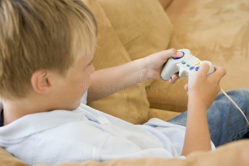 Menino novo na sala de visitas com jogo video imagem de stock