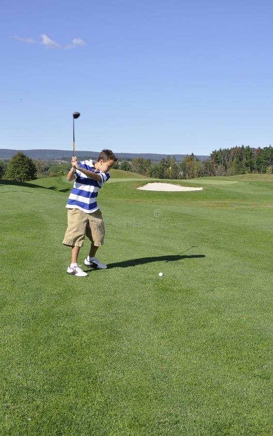 Menino novo no campo de golfe fotografia de stock royalty free