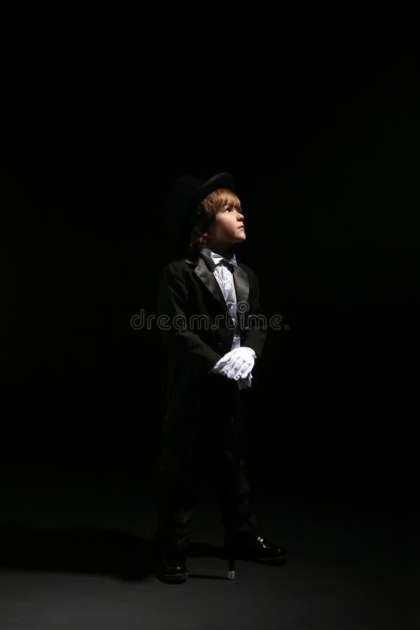 Menino novo no smoking preto que olha fora ao lado fotografia de stock royalty free