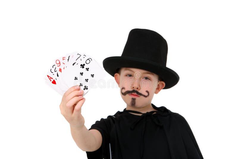 Menino novo no traje do mágico com cartões imagem de stock