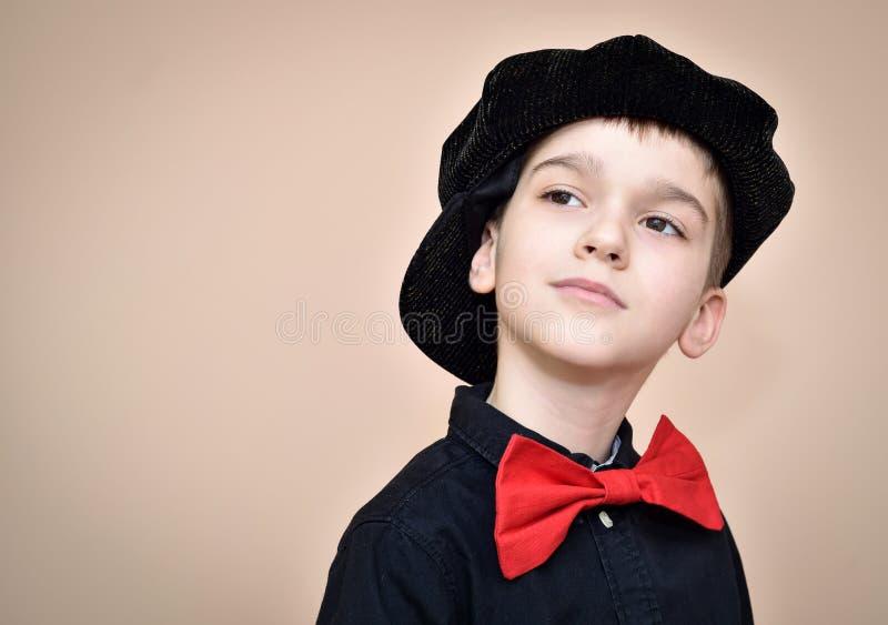 Menino novo pensativo com laço vermelho e camisa e tampão pretos imagem de stock