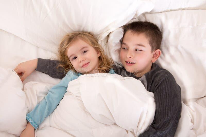 Menino novo protetor na cama com sua irmã mais nova fotos de stock royalty free
