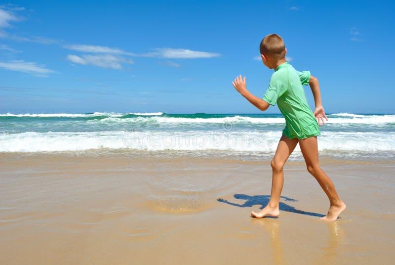 Menino novo que anda ao longo da praia imagem de stock royalty free
