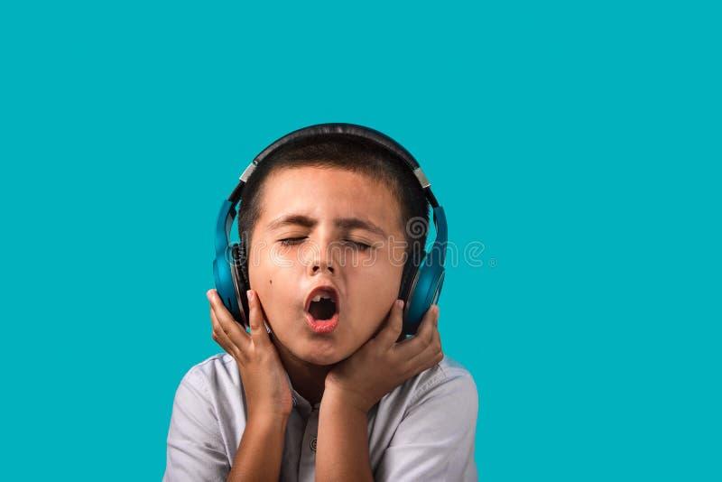 Menino novo que aprecia a música em seus fones de ouvido sem fio como guarda sobre e canta foto de stock royalty free