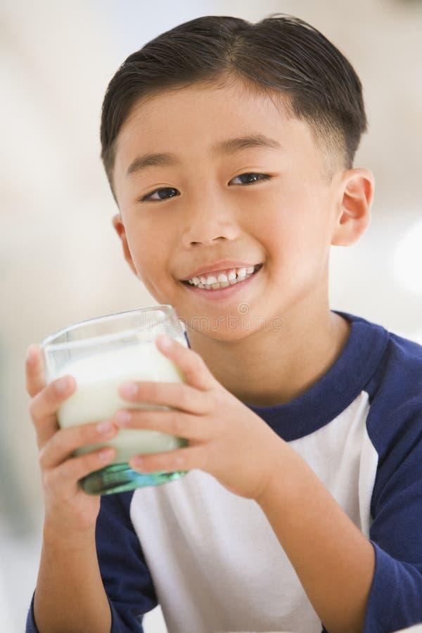Menino novo que bebe dentro o leite imagens de stock royalty free