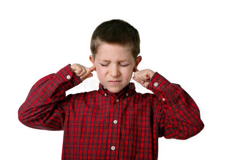 Menino novo que cobre suas orelhas, tiro do estúdio imagem de stock royalty free