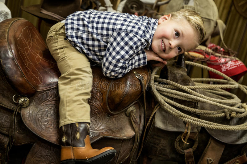 Menino novo que coloca em um sorriso ocidental da sela do vaqueiro foto de stock royalty free