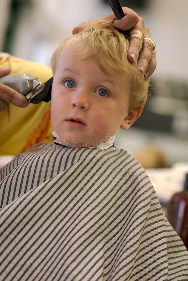 Menino novo que começ um corte de cabelo fotos de stock