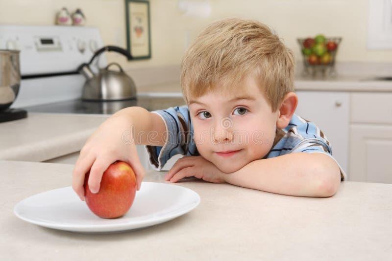 Menino novo que começ uma maçã para um petisco imagem de stock