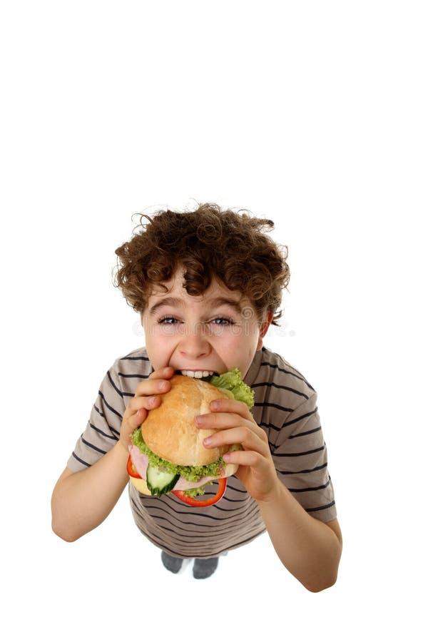 Menino novo que come o sanduíche saudável imagem de stock