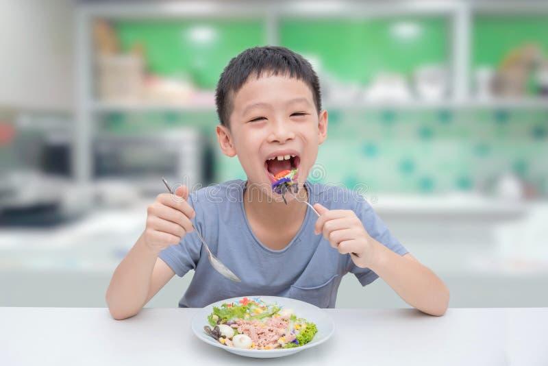 Menino novo que come a salada dos vegetais foto de stock royalty free