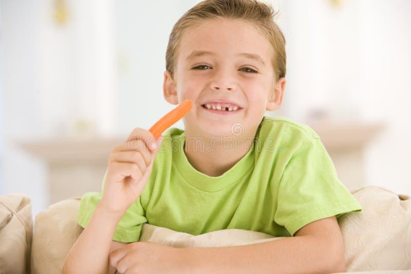 Menino novo que come a vara de cenoura na sala de visitas imagem de stock royalty free