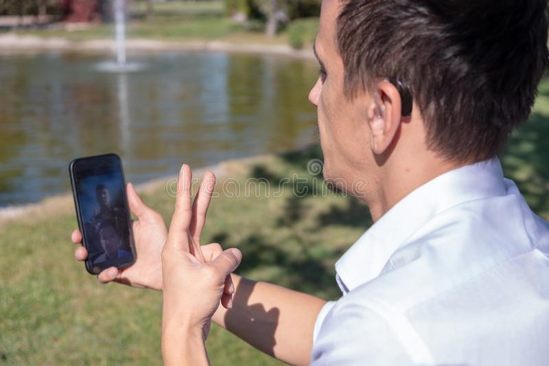Menino novo que comunica-se com a linguagem gestual no telefone esperto imagens de stock royalty free