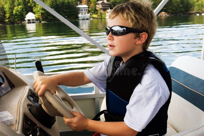 Menino novo que conduz um barco fotos de stock