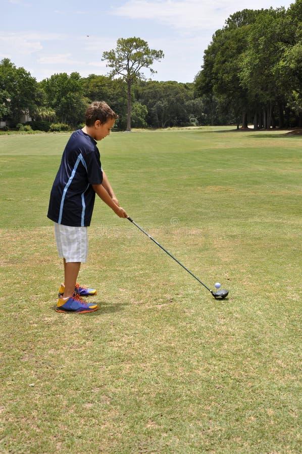 Menino novo que conduz uma esfera de golfe fotografia de stock royalty free
