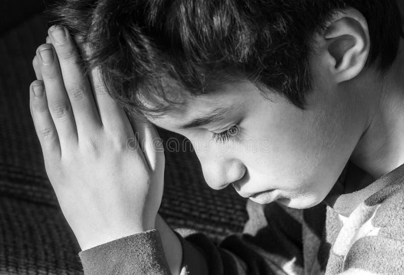 Menino novo que curva sua cabeça e que reza solenemente, preto e branco fotografia de stock